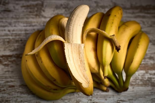 Manojo de sabrosos plátanos amarillos maduros en una tabla de madera ligera