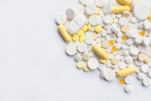Un manojo de tabletas y píldoras amarillas y blancas aisladas en un cierre blanco del fondo para arriba.