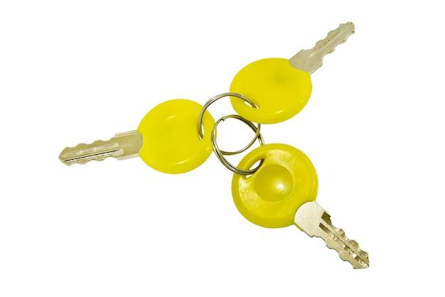 Un manojo de tres pequeñas llaves aisladas sobre una superficie blanca