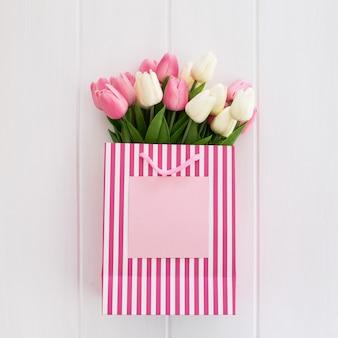 Manojo de tulipanes rosados y blancos en bolso de compras rosado fresco