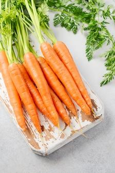 Manojo de zanahorias frescas en tabla de cortar de madera.
