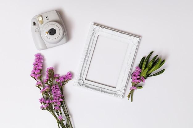 Manojos de flores cerca de marco de fotos y cámara