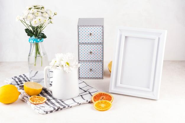 Manojos de flores frescas en jarrón y jarra cerca de frutas y marco de fotos