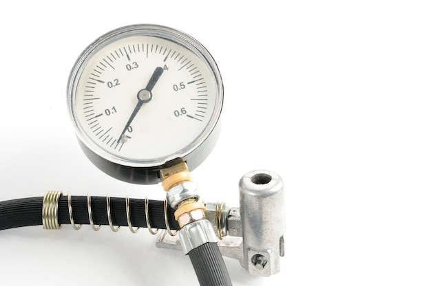 Manómetro para medir la presión del aire en los neumáticos de automóviles de cerca en un blanco aislado