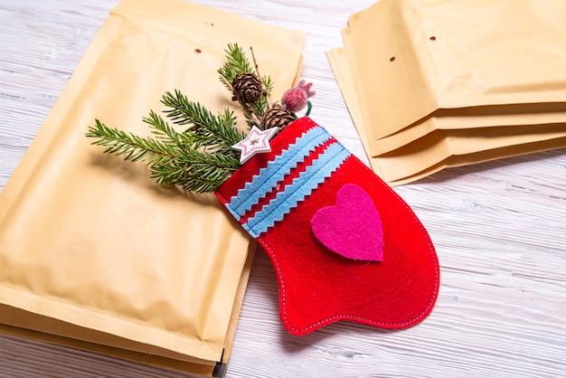 Manoplas hechas a mano y sobres postales en el escritorio de oficina, concepto de regalo de navidad
