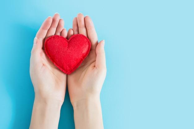 Las manos abiertas de la hembra que llevan a cabo un corazón rojo en un fondo azul copian el espacio para el texto. donación, concepto de atención médica.
