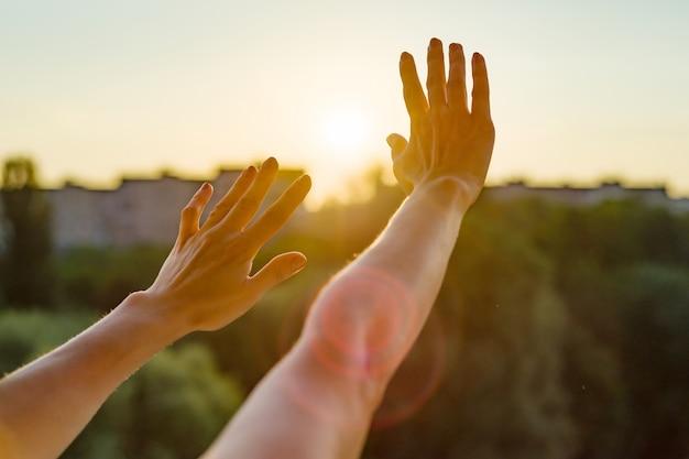 Manos abiertas a la puesta del sol