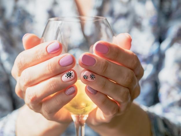 Las manos abrazan una copa de vino. manicura creativa con corona pintada.