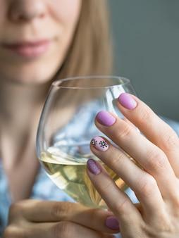 Las manos abrazan una copa de vino. manicura creativa con coronavirus pintado en las uñas, enfoque suave, primer plano
