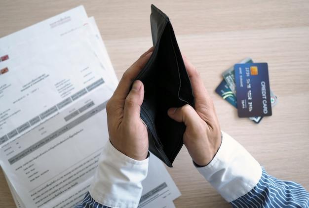 Las manos abren el bolso vacío. facturas y tarjetas de crédito pendientes de pago.