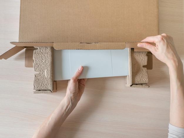 Las manos abren la caja. desempacando el paquete recibido