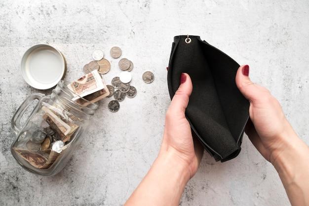 Manos abriendo cartera con jarra de ahorros
