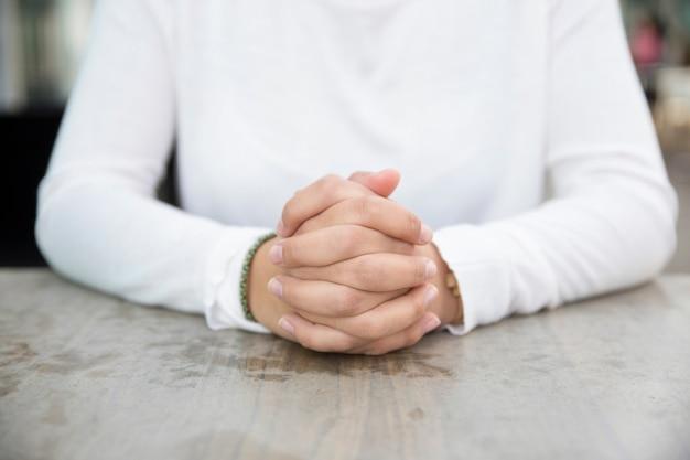 Manos abrochadas de joven empresaria sentado en la mesa