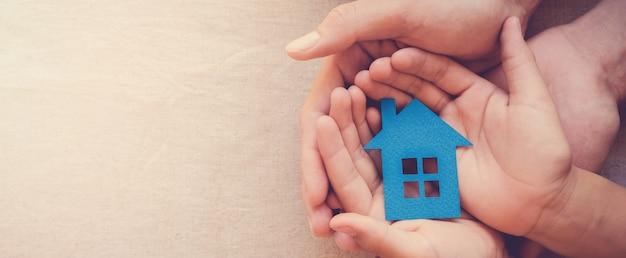Manos del adulto y del niño que sostienen la casa de papel, el hogar de la familia y el concepto de las propiedades inmobiliarias