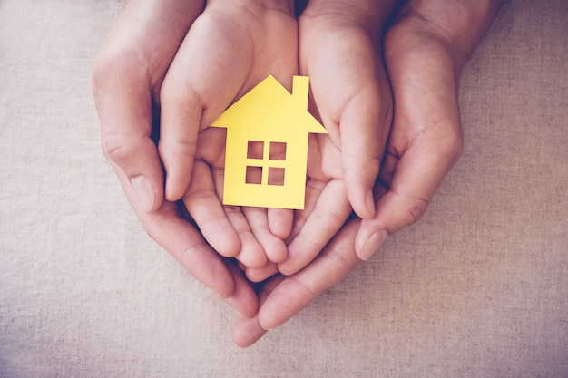 Manos de adultos y niños con casa amarilla, hogar familiar y concepto de refugio para personas sin hogar