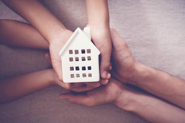 Manos de adultos y niños con casa blanca, hogar familiar y concepto de refugio para personas sin hogar