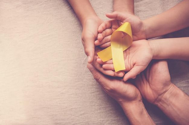 Manos de adultos y niños con cinta de oro amarillo.