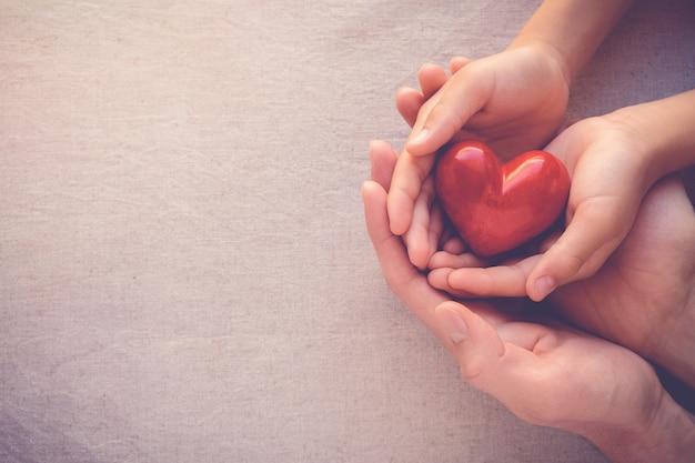 Manos de adultos y niños con corazón rojo, amor por el cuidado de la salud y concepto de familia