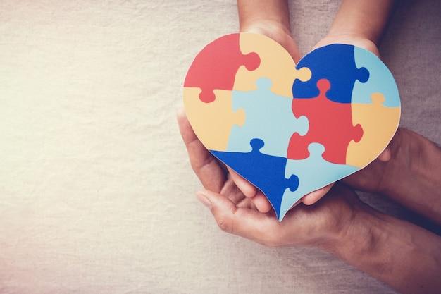 Manos de adultos y niños con corazón de rompecabezas, concepto de salud mental, día mundial de concienciación sobre el autismo
