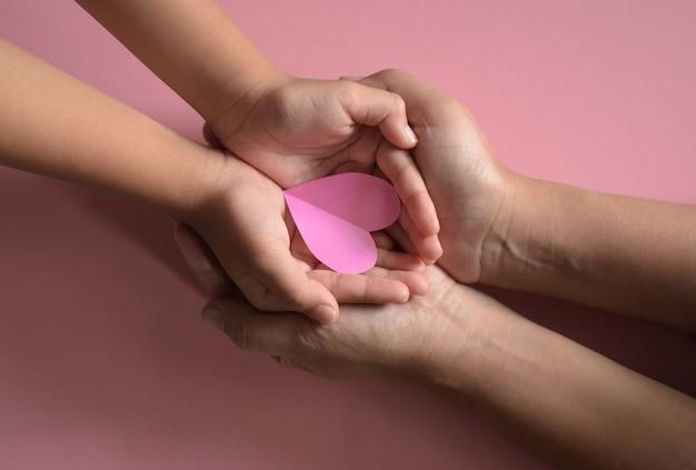 Manos de adultos y niños con corazón rosa sobre fondo rosa amor seguro familiar de salud