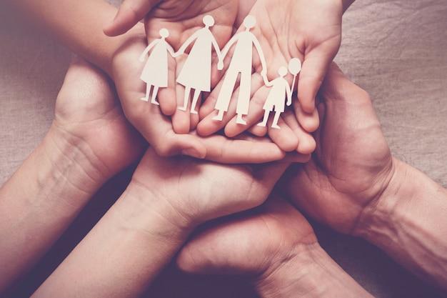 Manos de adultos y niños con papel recorte familiar, hogar familiar,