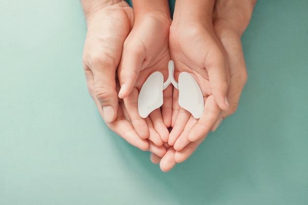 Manos de adultos y niños con pulmón, día mundial de la tuberculosis, día mundial sin tabaco, virus corona covid-19, contaminación del aire ecológica. concepto de donación de órganos