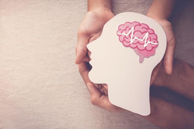 Manos de adultos y niños con recorte de papel encefálico encefalográfico, conciencia de epilepsia y alzheimer, trastorno convulsivo, concepto de salud mental
