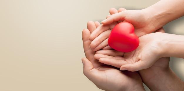 Manos de adultos y niños sosteniendo un corazón rojo sobre fondo aqua, salud del corazón, donación, concepto de rse,