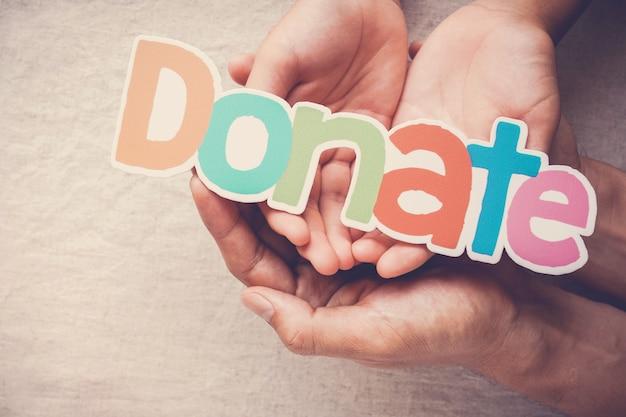Manos de adultos y niños sosteniendo la palabra donar, donación y concepto de caridad