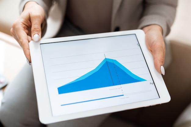 Manos de agente de bienes raíces sosteniendo tableta digital con gráfico financiero azul en pantalla mientras realiza la presentación al cliente