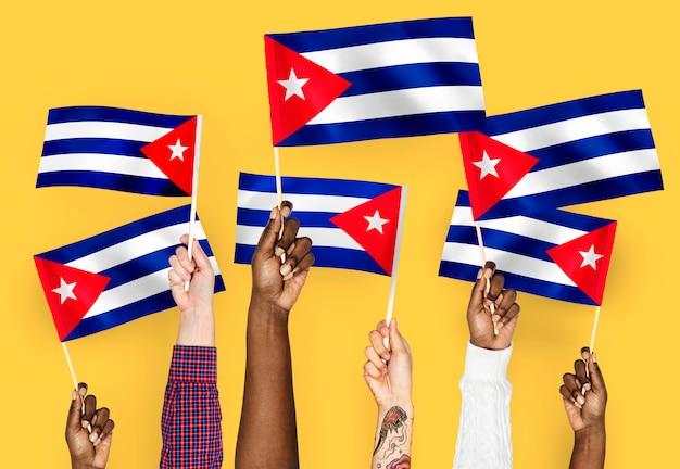 Manos agitando banderas de cuba