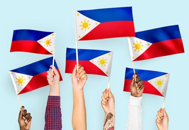 Manos agitando banderas de las filipinas