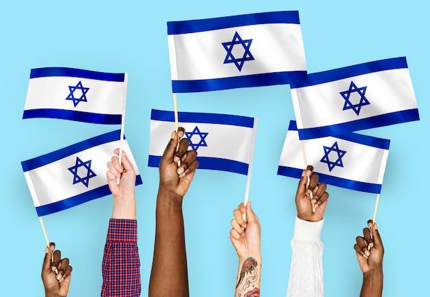 Manos agitando banderas de israel