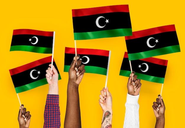 Manos agitando banderas de libia