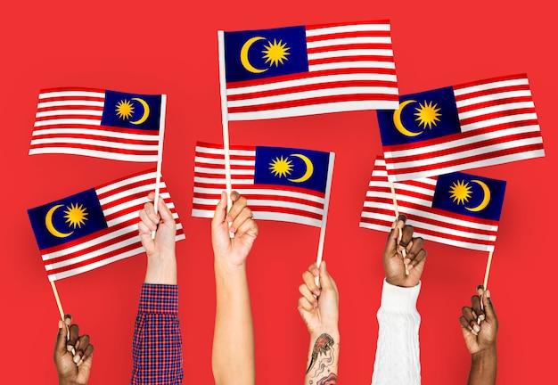 Manos agitando banderas de malasia