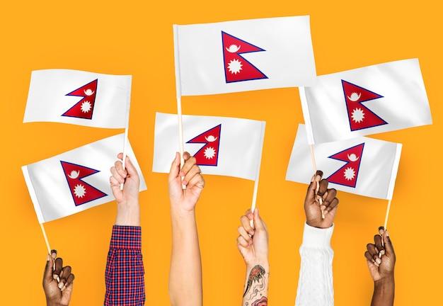 Manos agitando banderas de nepal