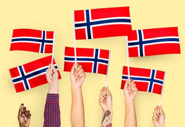 Manos agitando banderas de noruega