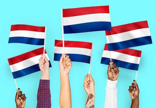 Manos agitando banderas de los países bajos