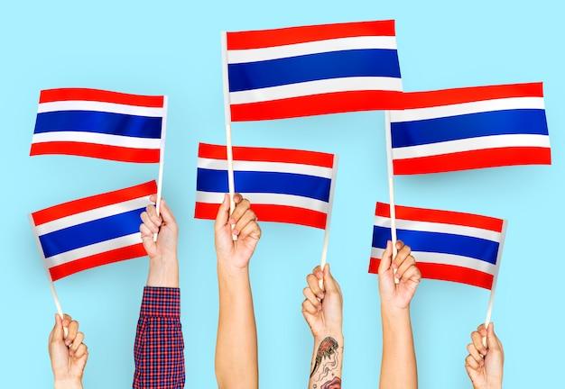 Manos agitando banderas de tailandia