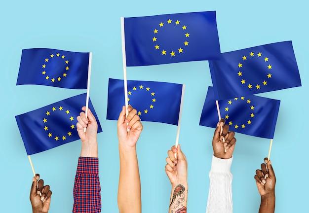 Manos agitando banderas de la unión europea.