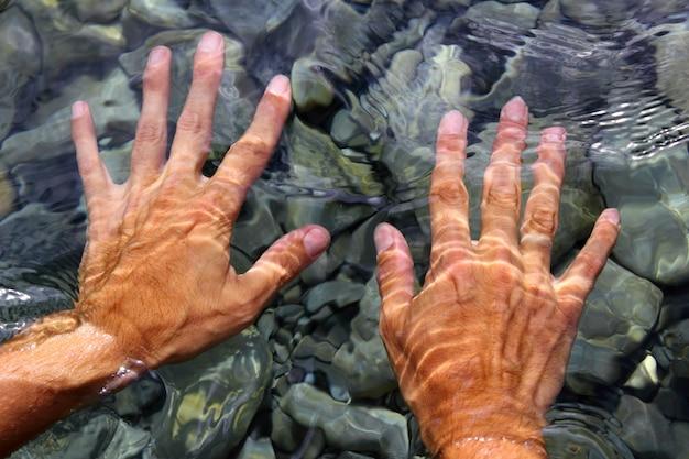 Manos bajo el agua del río formas onduladas de agua