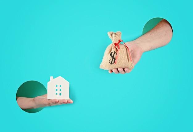 Manos en los agujeros de papel que sostienen la casa y una bolsa con dinero.