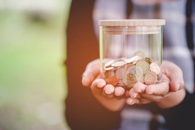 Manos y ahorros de mujeres jóvenes de cerca para negocios.