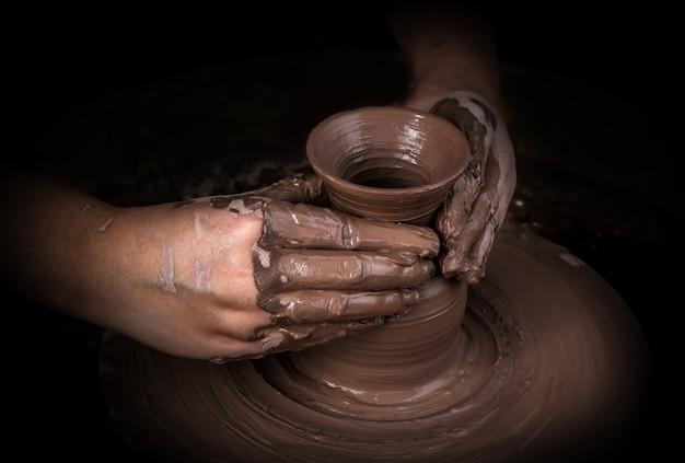 Manos de un alfarero, creando un tarro de barro en el círculo