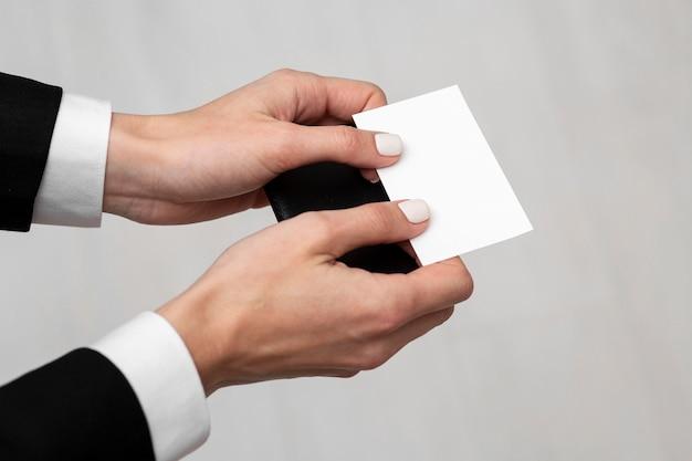 Manos de alta vista sosteniendo tarjetas de visita