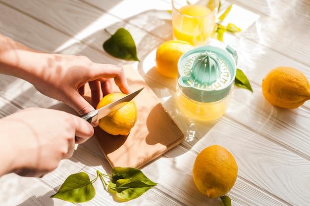 Manos de alto ángulo cortando limón