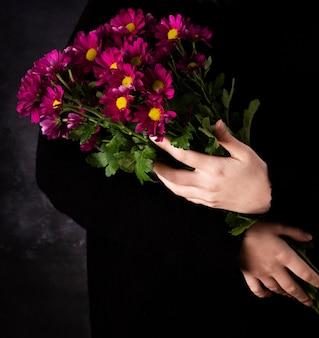 Manos de alto ángulo con ramo de flores