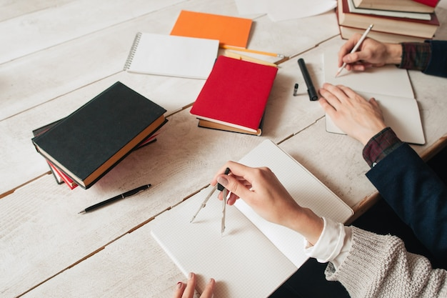 Manos de alumnos que estudian matemáticas en un escritorio con suministros