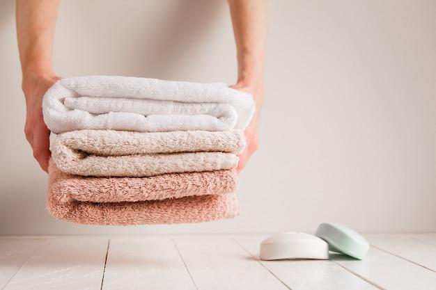 Las manos de las amas de casa ponen toallas en el estante de madera blanca del baño