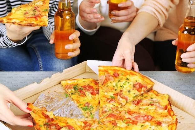 Manos de amigos con botellas de cerveza y pizza, cerrar